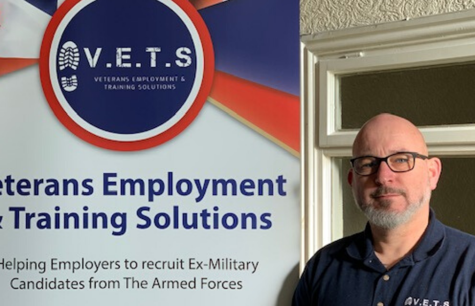 Paul Lewis standing by Veterans Employment sign